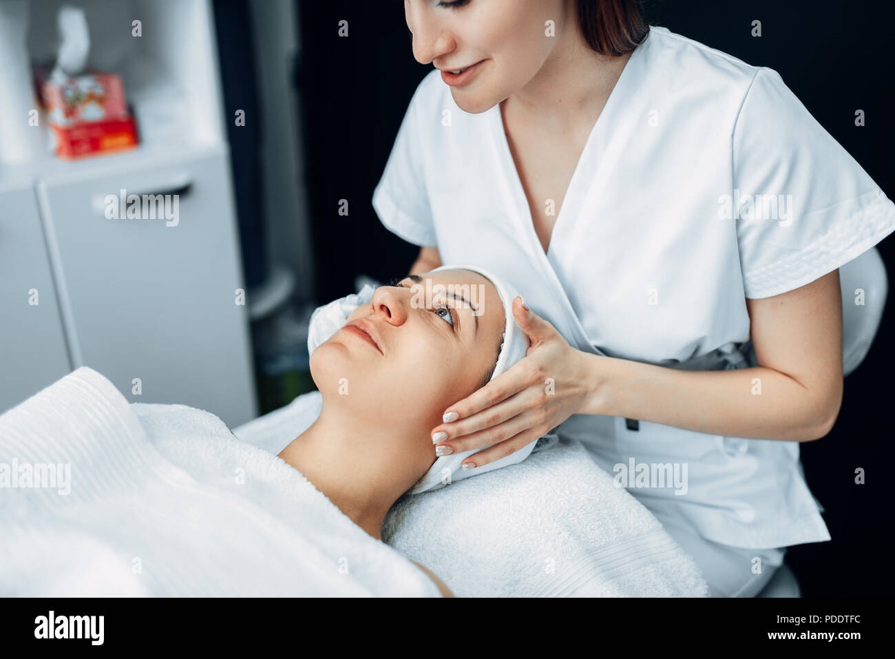 Face massage to female patient, cosmetology clinic - Stock Image