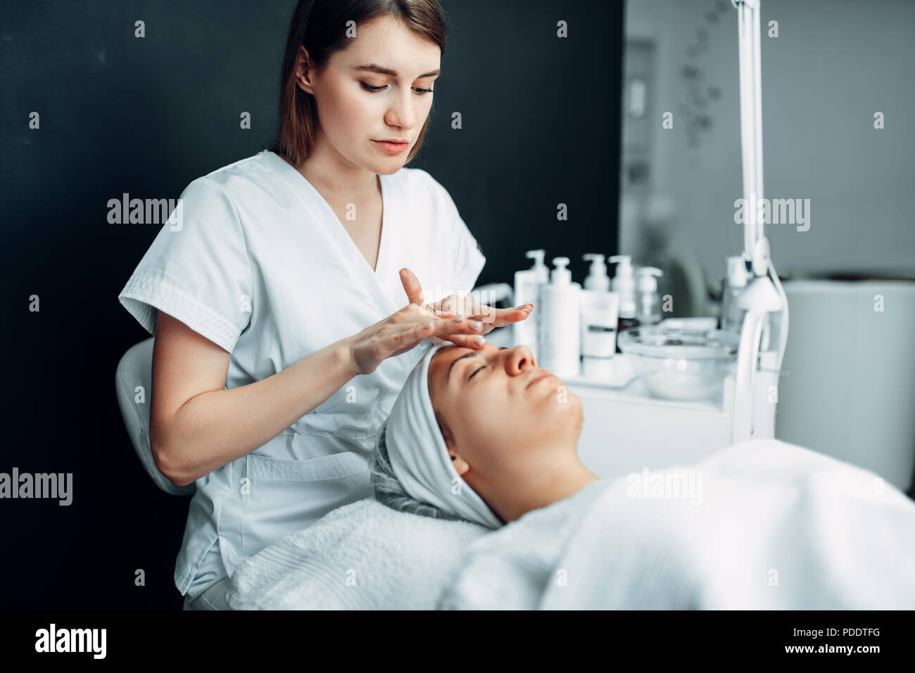 Beautician rubs the cream on female patient face - Stock Image