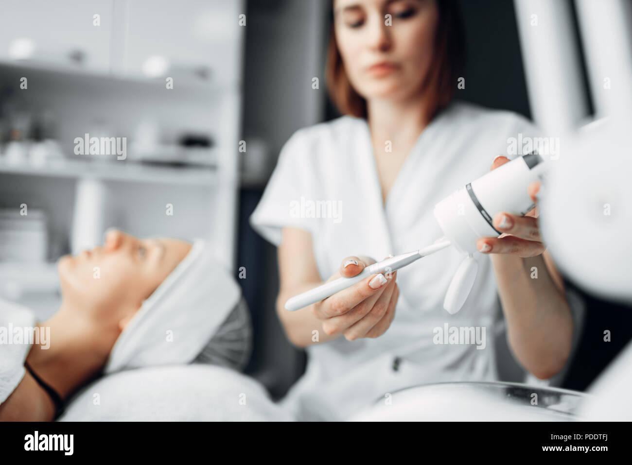 Beautician prepares laser, rejuvenation procedure - Stock Image