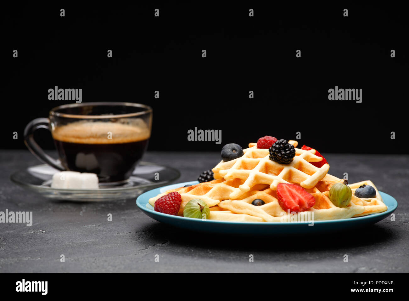 Photo of cup of coffee with sugar with Viennese waffles with strawberries, raspberries - Stock Image