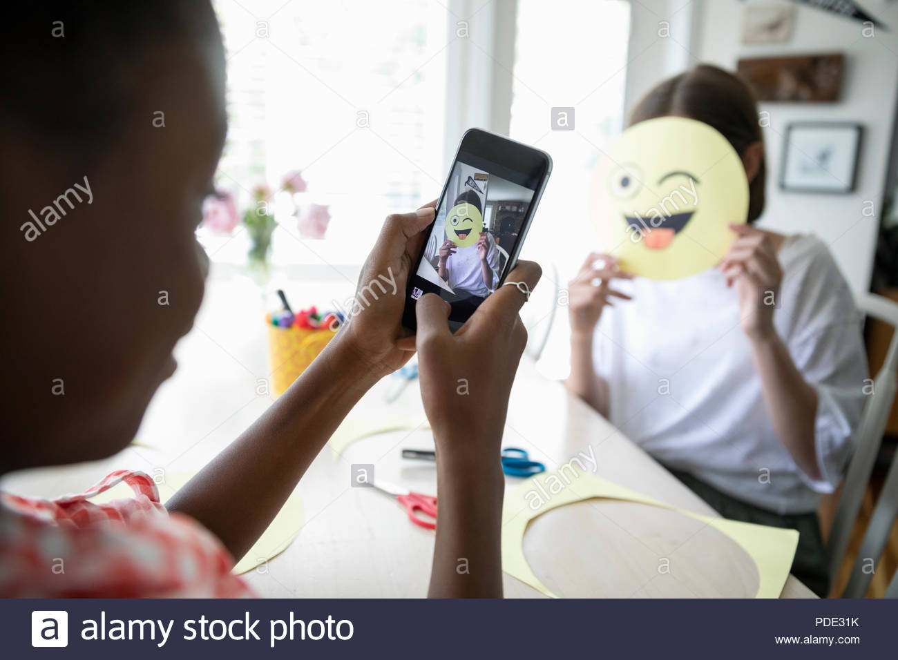Tween girl with camera phone photographing friend holding winking emoji art project - Stock Image