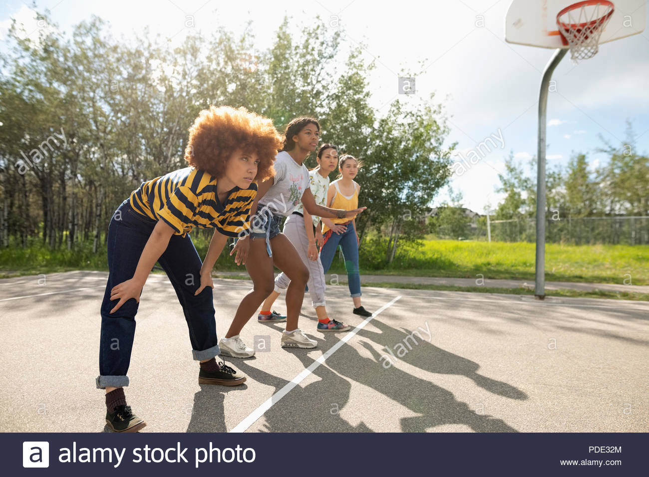 Teenage girl friends playing basketball at park basketball court - Stock Image