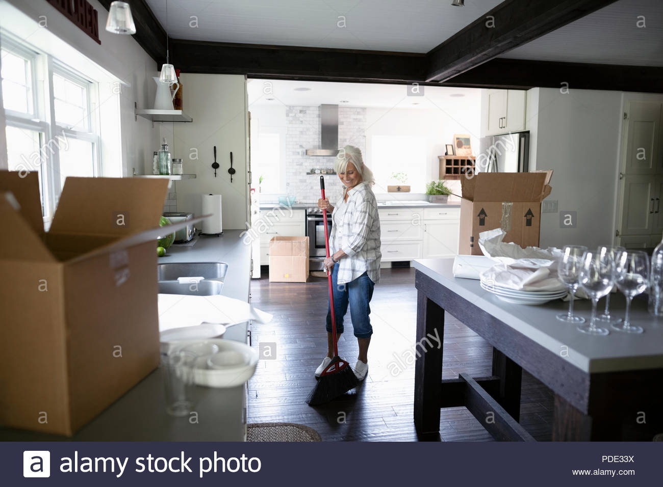 Senior woman downsizing, packing and sweeping kitchen - Stock Image