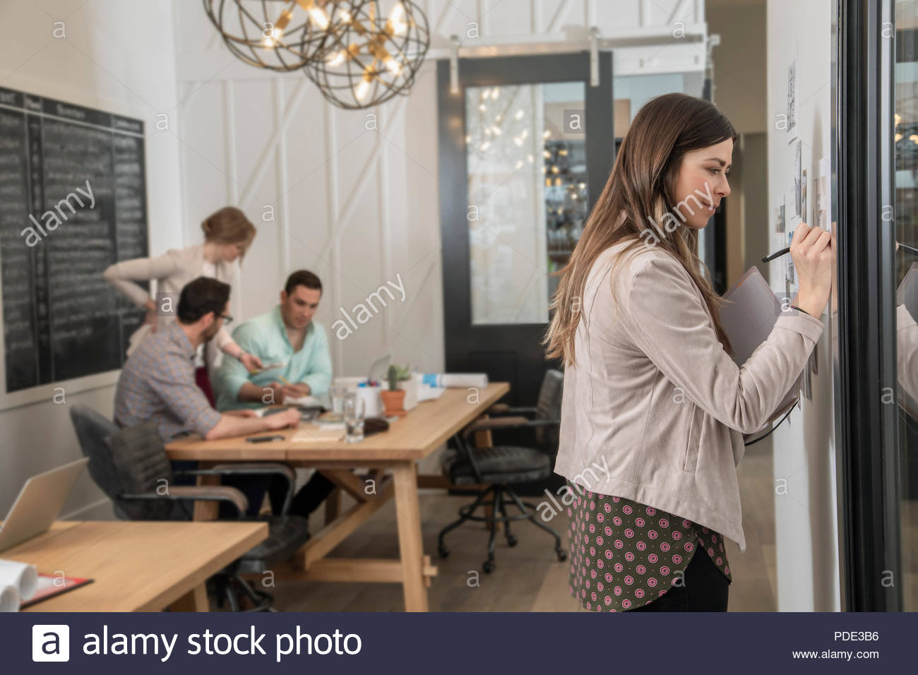 Female home builder architect planning at wall in office - Stock Image