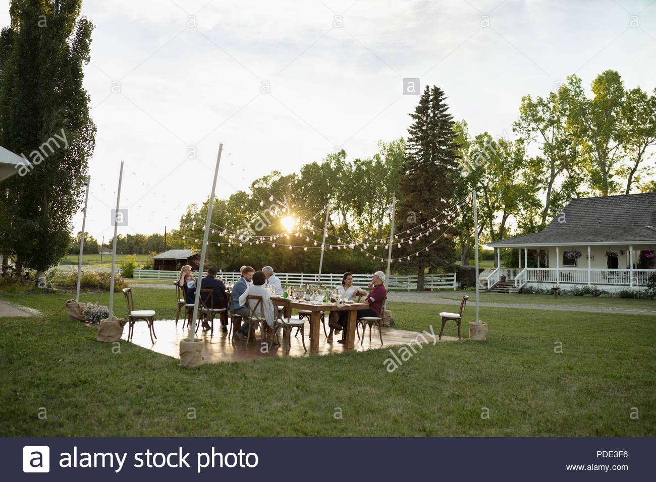 Friends eating and drinking at wedding reception table in rural garden - Stock Image