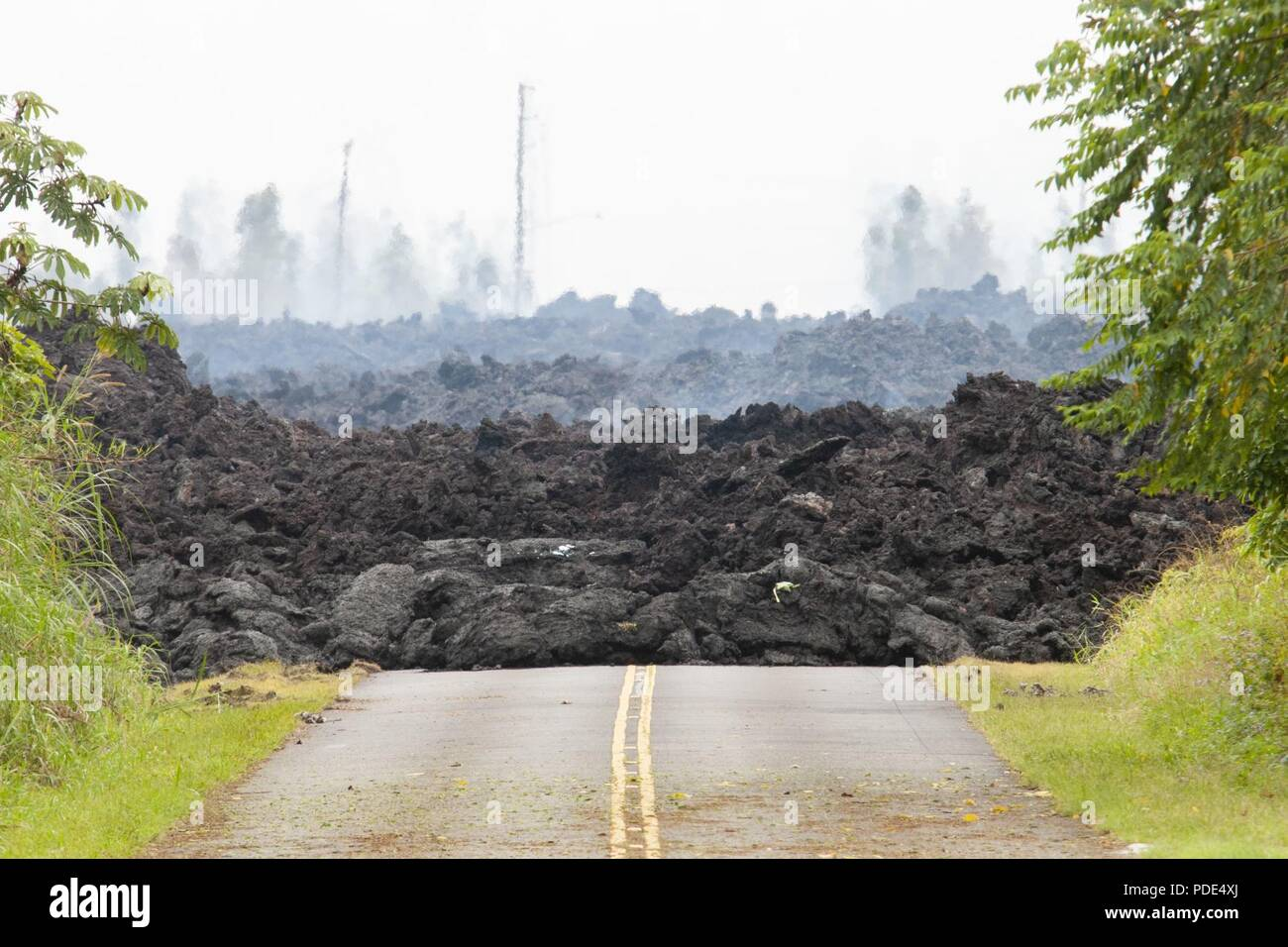 A lava roadblock covers a residential road May 12, 2018, at Leilani Estates, Pahoa, Hawaii. Members of the Hawaii Army and Air National Guard have been activated in order to assemble Task Force Hawaii, which is providing traffic assistance, presence patrols and supporting local government agencies with the volcano outbreak relief effort. Stock Photo