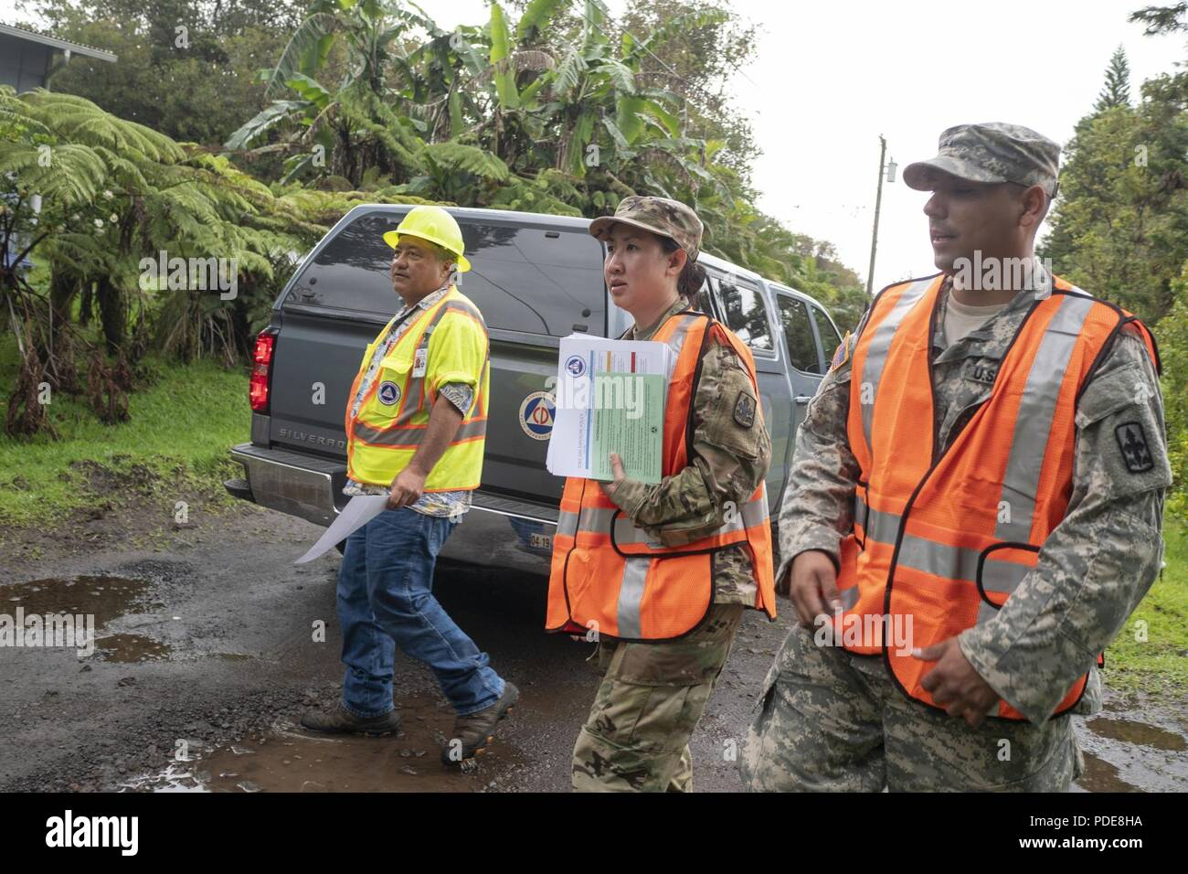 William Hanson, County of Hawaii Civil Defense administrative officer, Spc. Anyanee Sangchan and Sgt. Ambrose Leon, representatives of Task Force Hawaii, approach residents of the Volcano community May 17, 2018, at Upper Puna District, Hawaii. Teams went door-to-door to inform local residents of the heightened risks, due to the ongoing volcanic activity in the area. - Stock Image