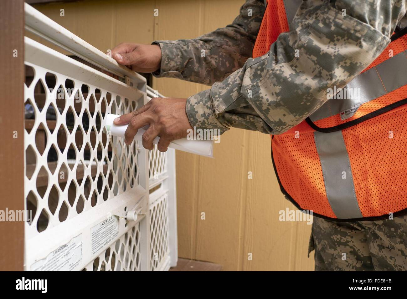 A Hawaii Army National Guard soldier leaves a leaflet at a resident's house community May 17, 2018, at Upper Puna District, Hawaii. Representatives from Task Force Hawaii supported the County of Hawaii Civil Defense's effort in informing residents of potential hazards and precautions to take in response to the ongoing volcanic activity. - Stock Image