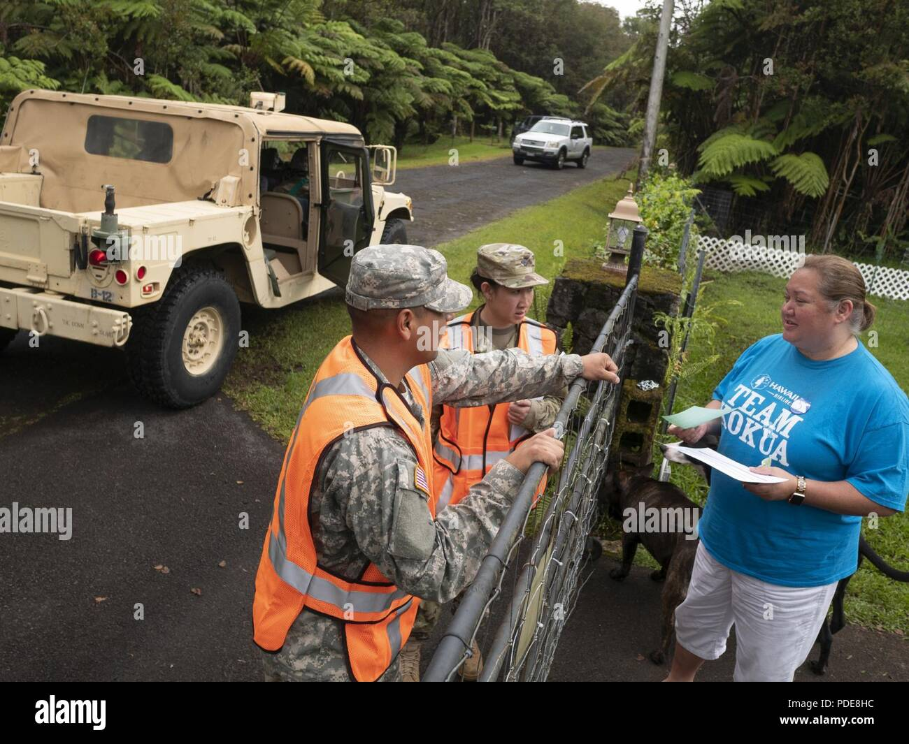 Sgt. Ambrose Leon and Spc. Anyanee Sangchan, representatives of Task Force Hawaii, speak to Kina Sai, a resident of the Volcano community May 17, 2018, at Upper Puna District, Hawaii. Residents have been visited by guardsmen and members of County of Hawaii Civil Defense as a measure to ensure the community is informed about the adverse conditions which may occur, due to the ongoing volcanic activity. - Stock Image