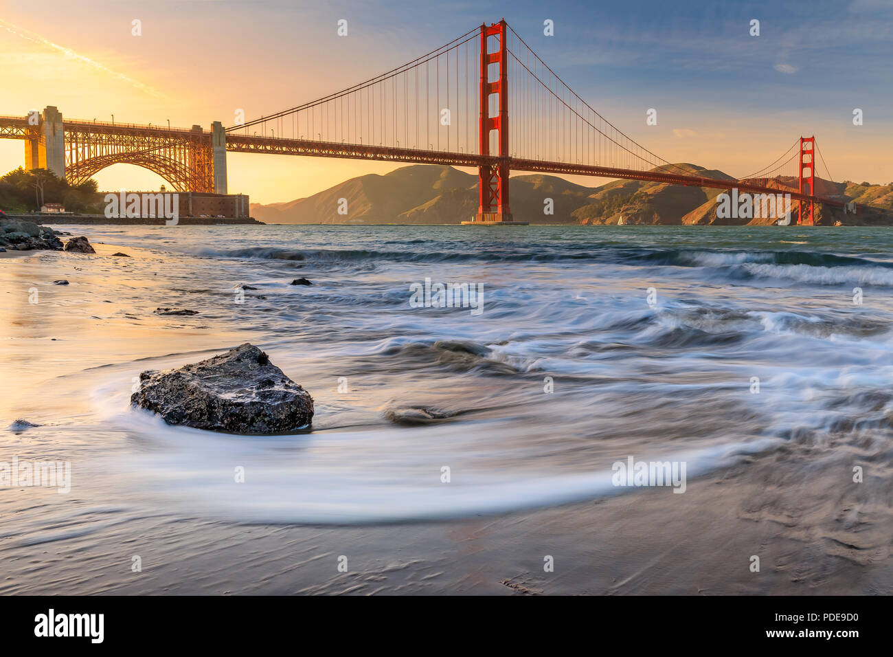 Long exposure of a stunning sunset at the beach by the famous Golden Gate Bridge in San Francisco, California - Stock Image