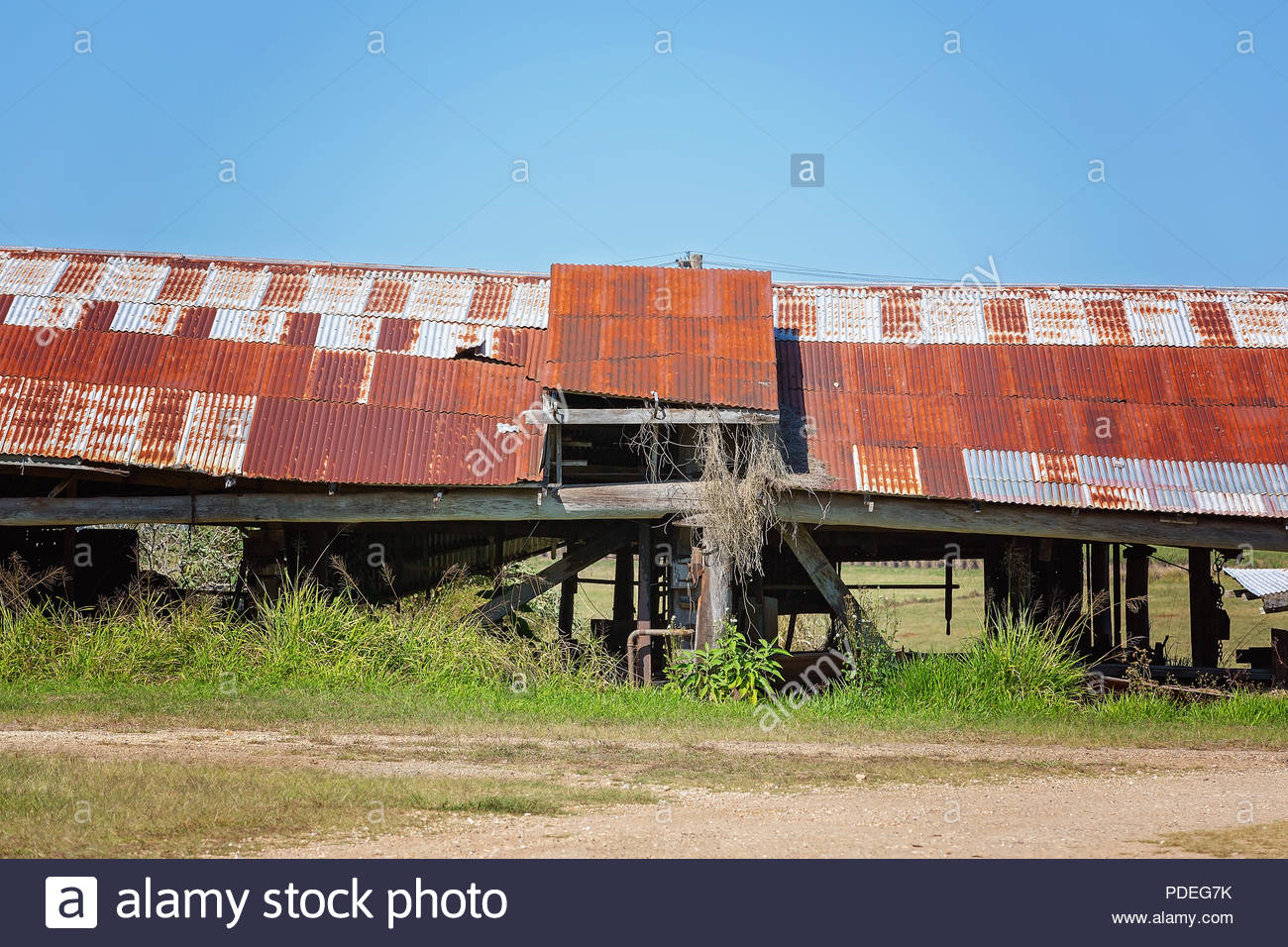A long low decrepit old shed with rusted iron roof against a blue sky background - Stock Image