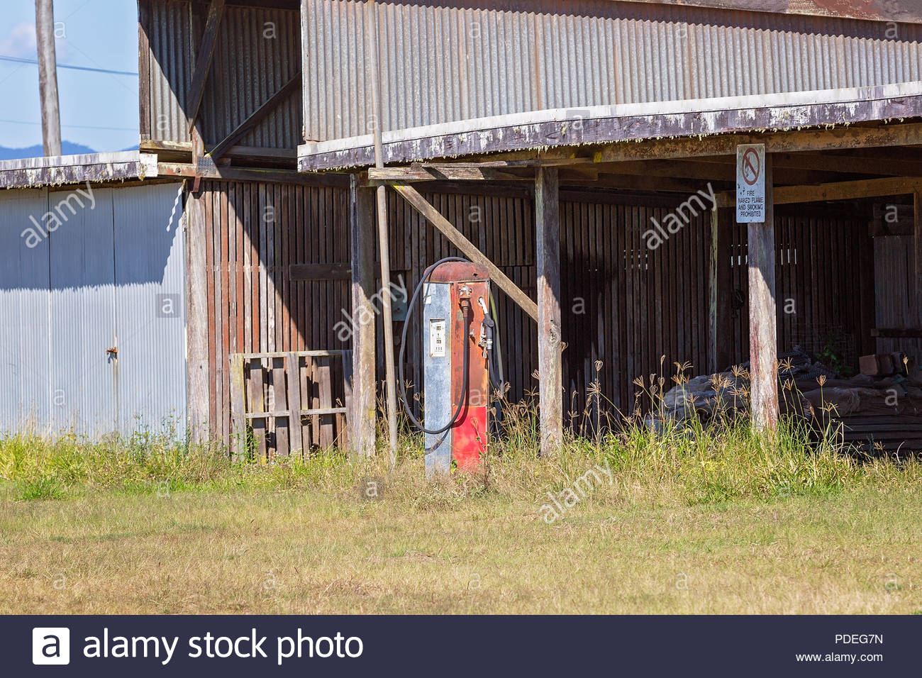 An old decrepit shed with disused petrol pump at front - Stock Image
