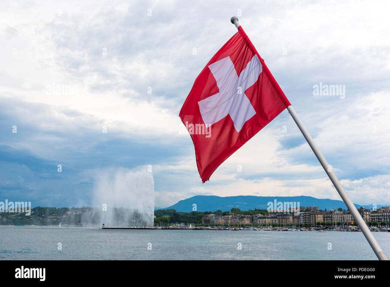 National flag of Switzerland flying from a pole on Pont du Mont Blanc with the Jet d'eau in the background - Stock Image