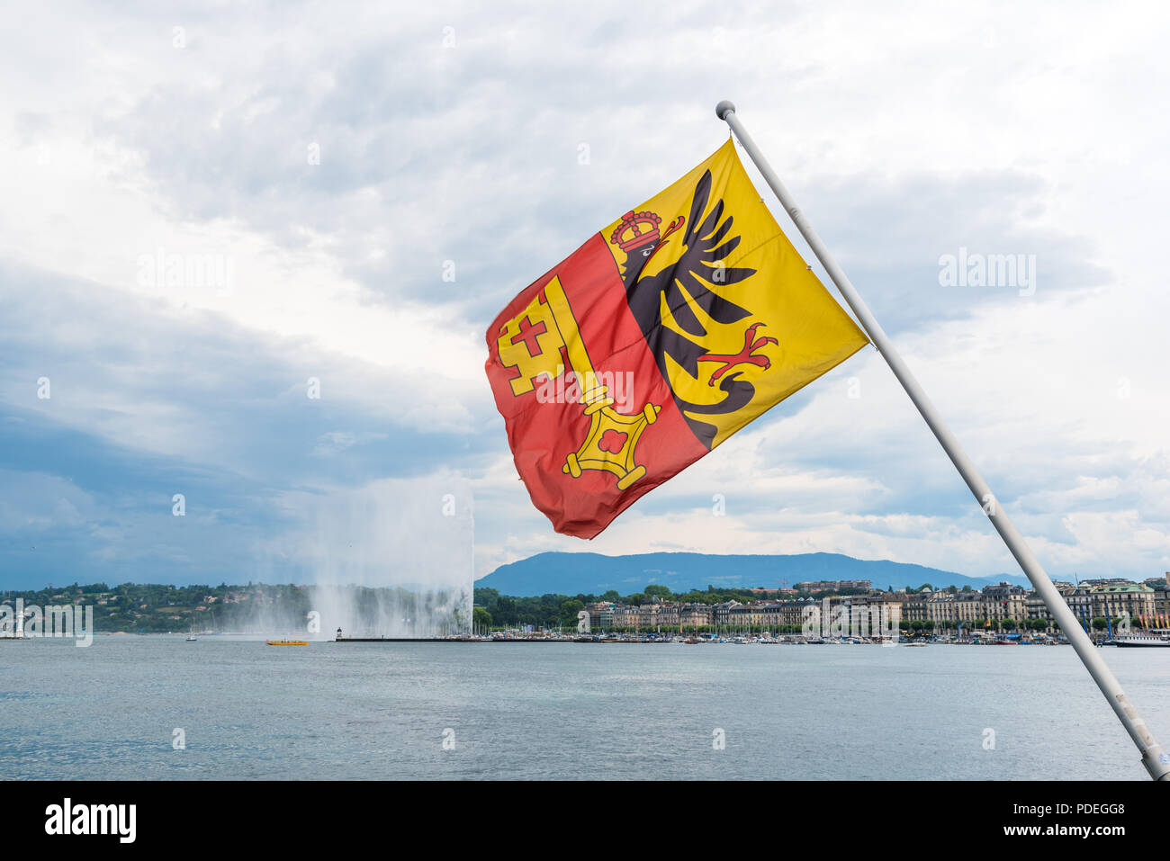 Flag of the Bishopric of Geneva flying from a pole on Pont du Mont Blanc on the banks of Lac Leman in Geneva with the Jet d'eau in the background - Stock Image