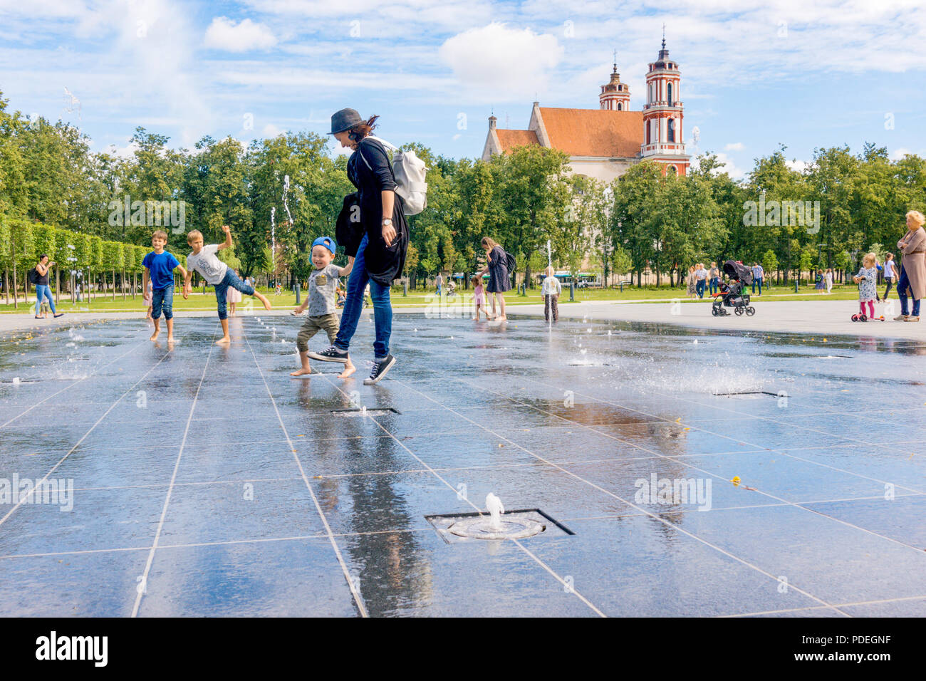 People have fun playing in city water fountain on hot summer day in Lukiskes square. - Stock Image
