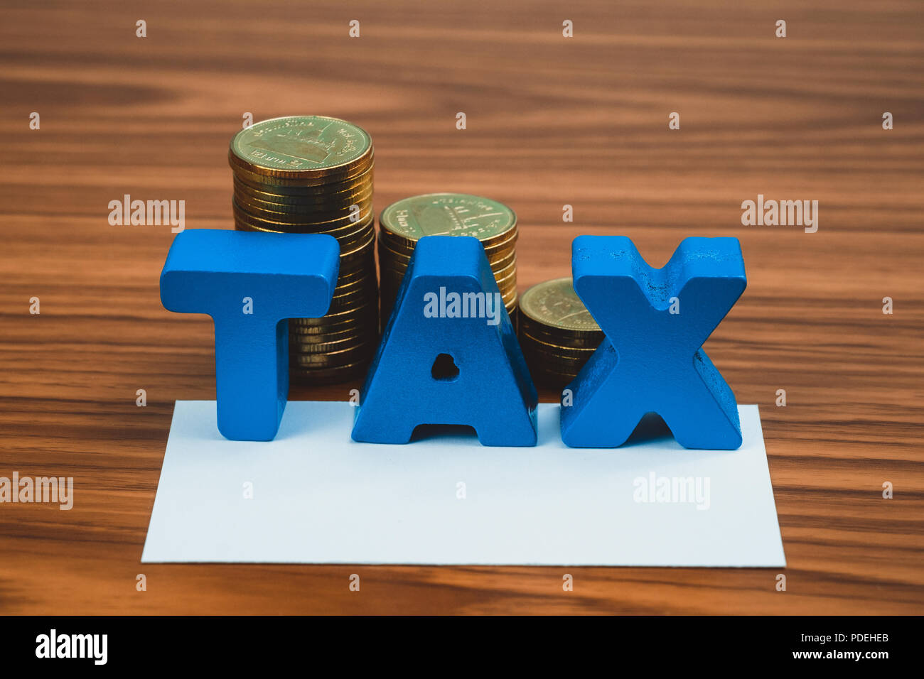 Tax concept tax alphabet with stack of coin and business card or tax alphabet with stack of coin and business card or name card on wooden working table business and financial concept idea colourmoves