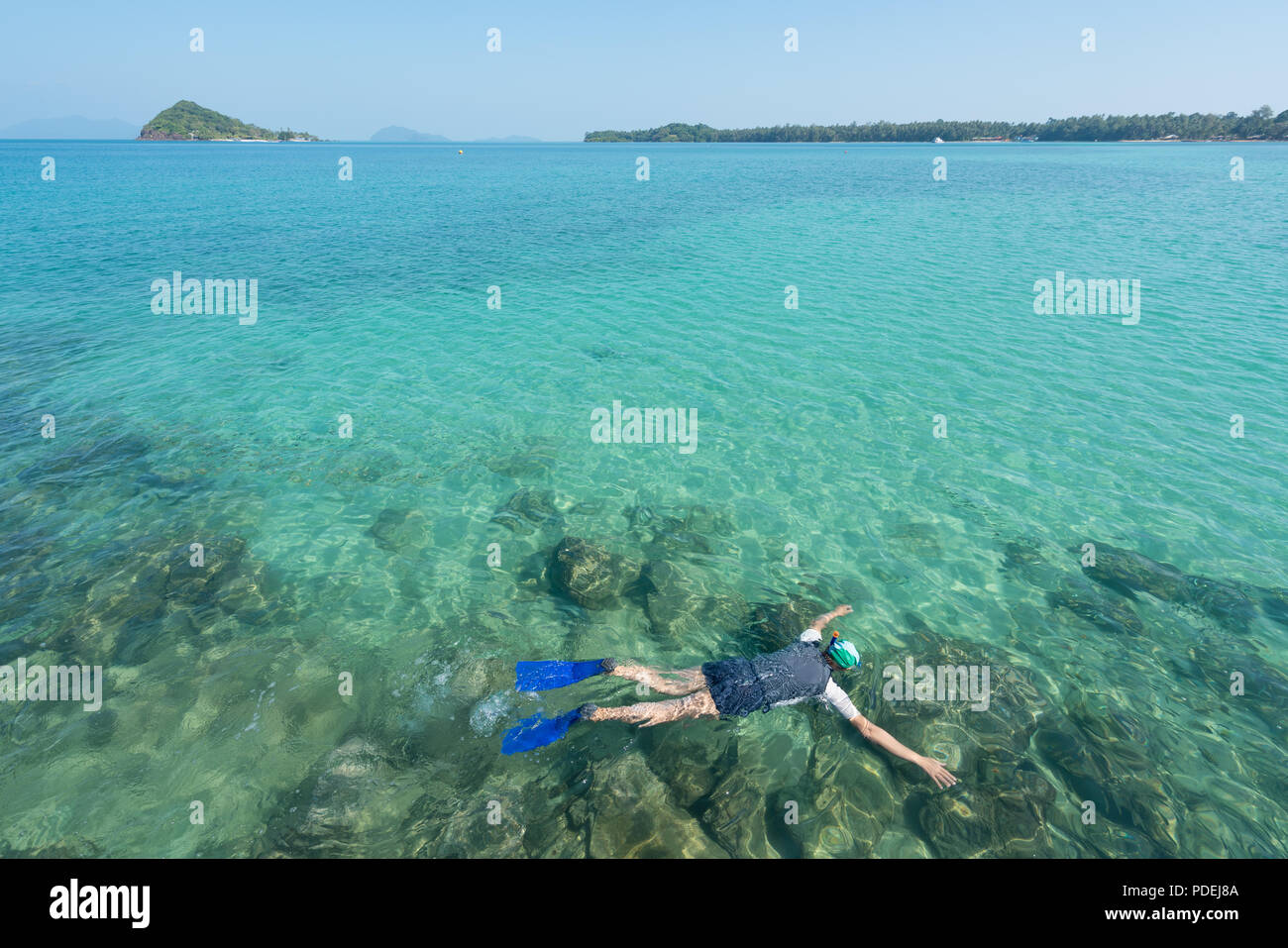 Tourists snorkel in crystal turquoise water near tropical resort in Phuket, Thailand. Summer, Vacation, Travel and Holiday concept. - Stock Image