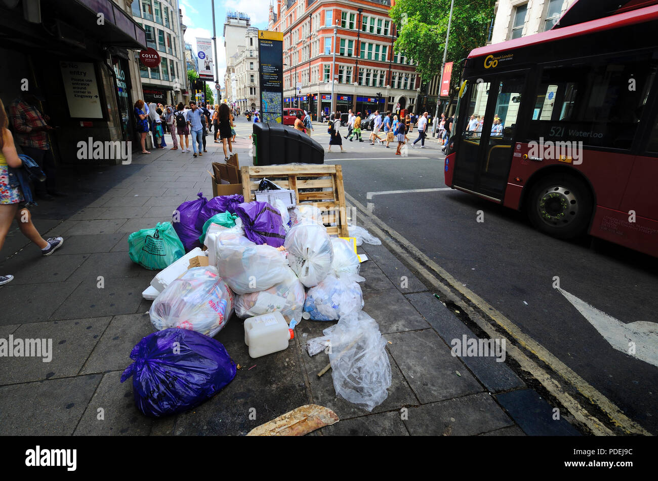 London, England, UK. Rubbish bags piled up by a bin in central London - Stock Image