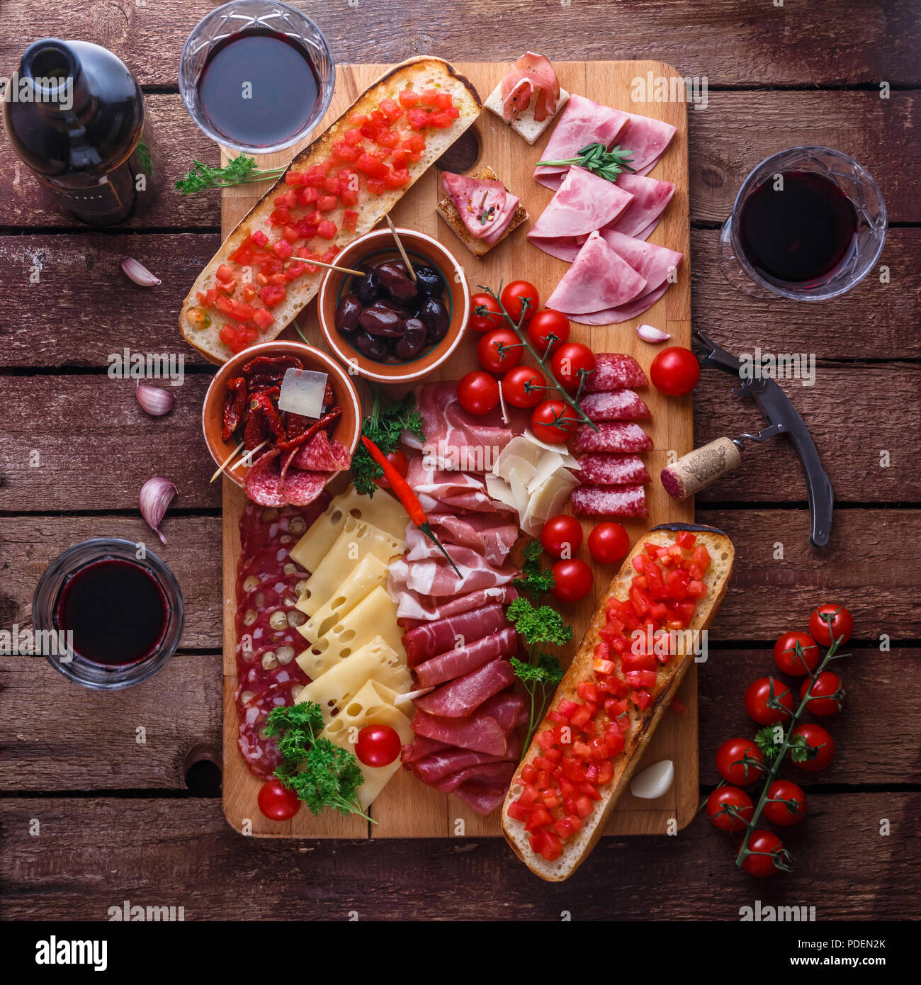 Red wine with charcuterie assortment on dark rustic table, flat lay - Stock Image