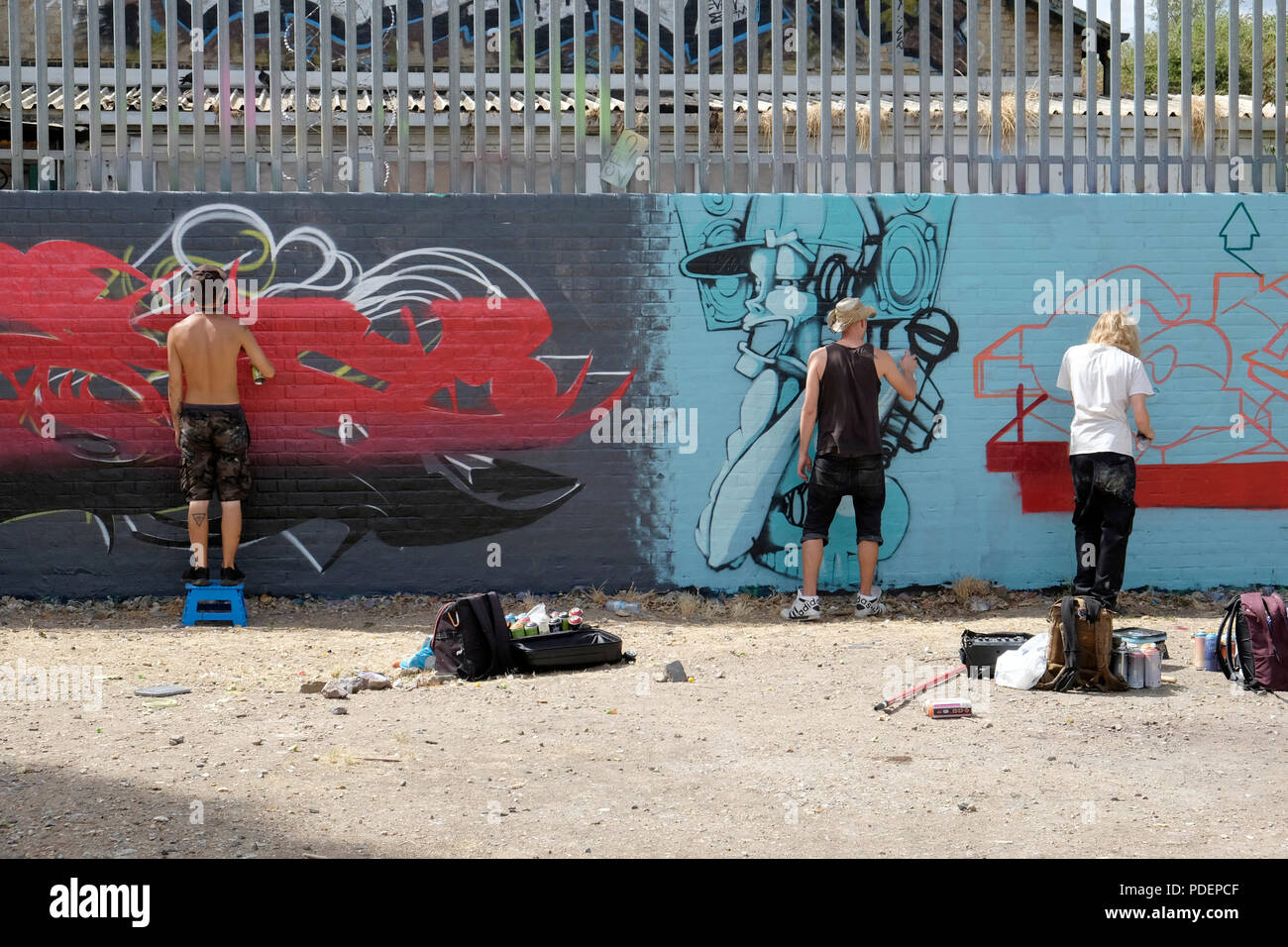 Three graffiti artists work on a mural in brick lane london stock image