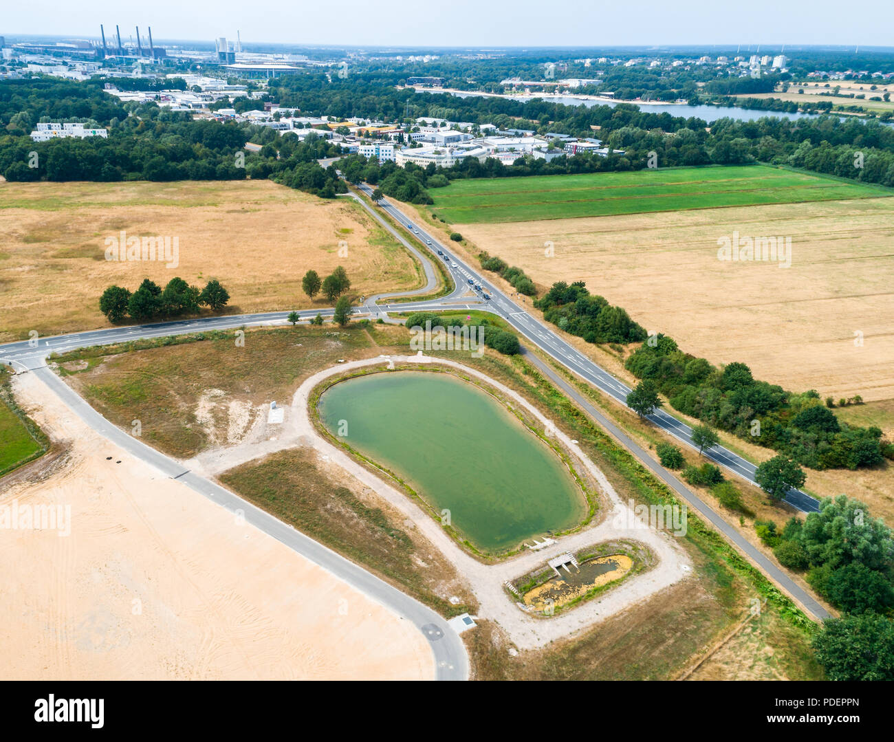 Aerial view of a rain retention basin at the edge of a new development, taken oblique. - Stock Image