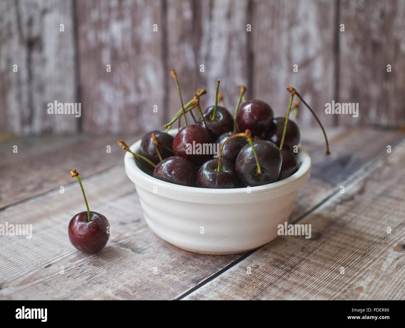 Appetizing Fresh Morello Cherries in white bowl on wooden table top - Stock Image