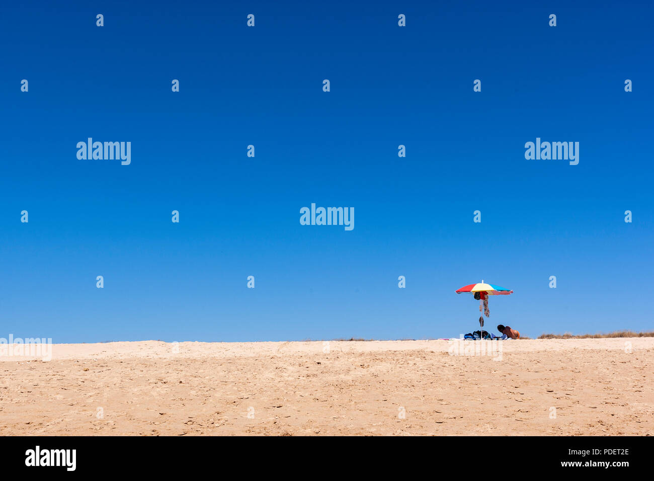 Isolated bather with parasol in the beach of Praia do Alvor, Alvor, Algarve, Portugal - Stock Image