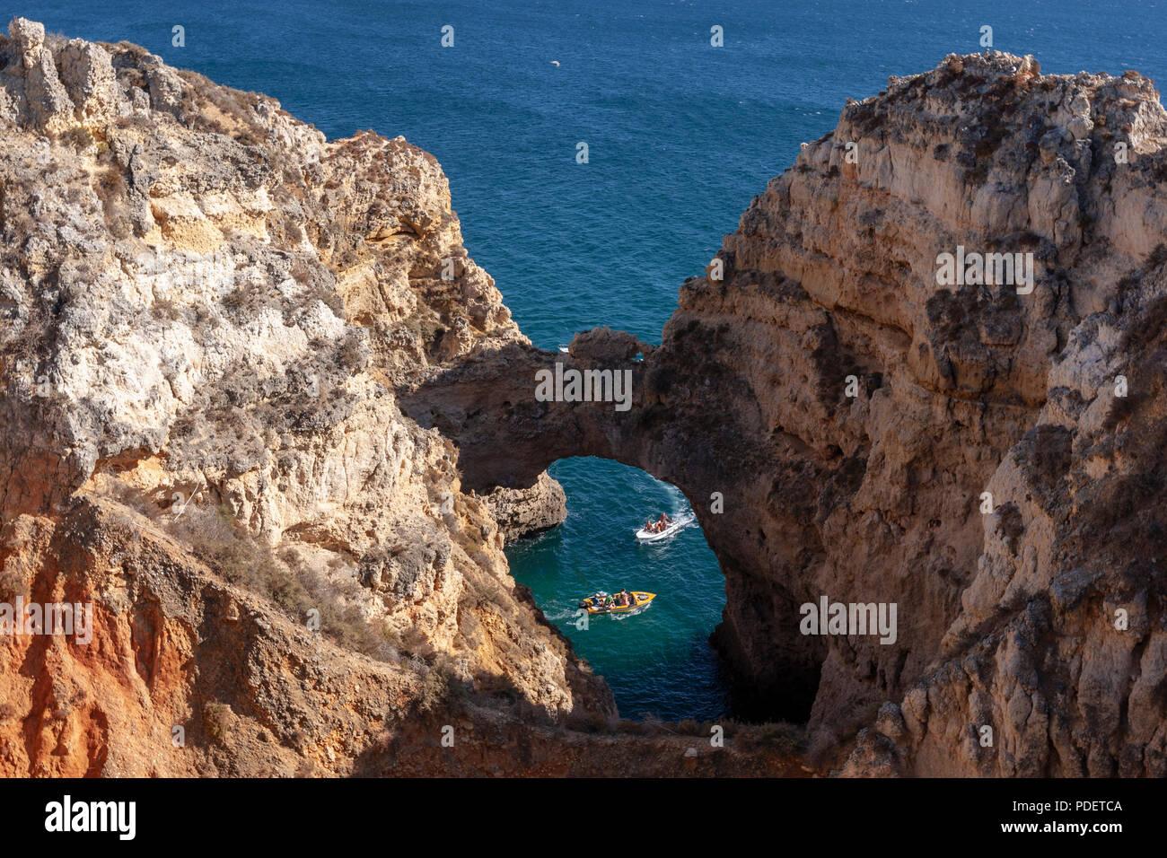 Tourists boats in a rocky arch in the rugged coastlines and sandstone cliffs near Farol da Ponta da Piedade, Lagos, Algarve, Portugal - Stock Image