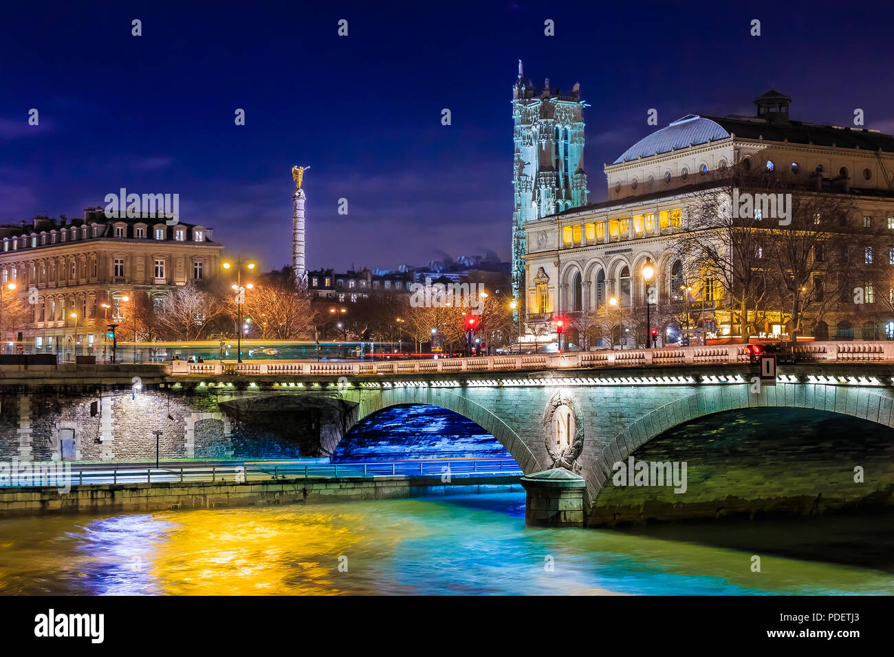 Twilight view onto the Seine at pont au Change bridge and the guilded and winged Statue de la Victoire or Victory Statue in Paris France - Stock Image