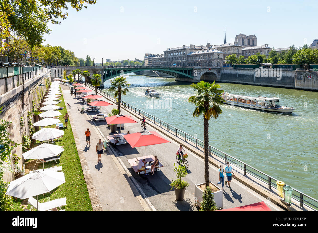 The banks of the Seine during Paris-Plages summer event in Paris, France, with boats passing by and Notre-Dame de Paris cathedral in the background. - Stock Image