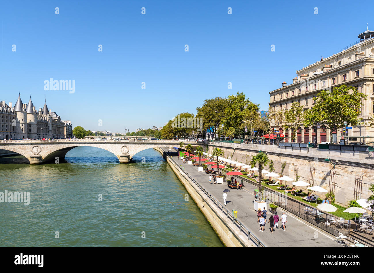 The banks of the Seine during Paris-Plages summer event in Paris, France, with the Pont au Change bridge and the Palais de la Cite in the background. - Stock Image