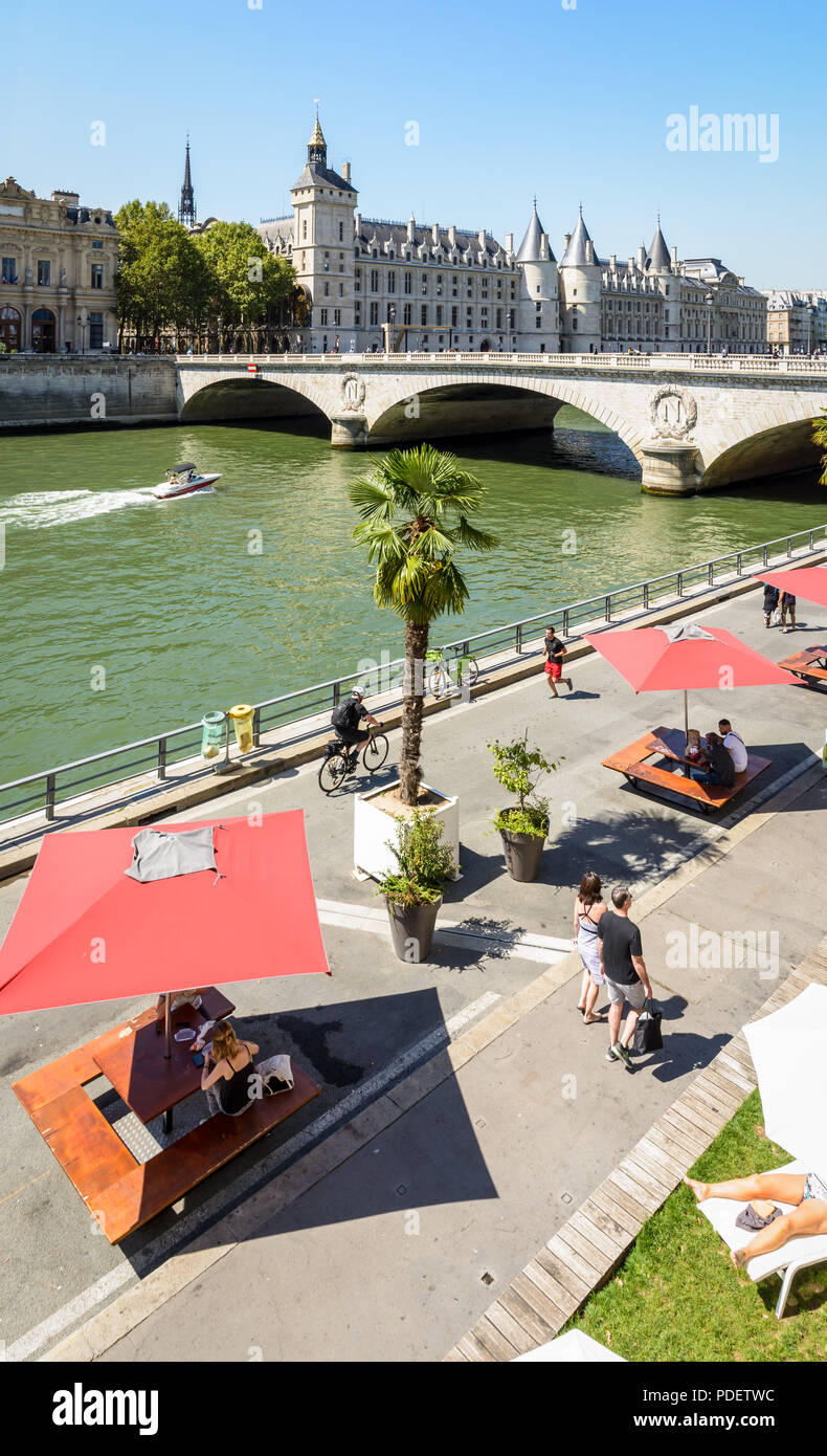 The banks of the Seine during Paris-Plages summer event with a motorboat passing under the Pont au Change and the Palais de la Cite in the background. - Stock Image