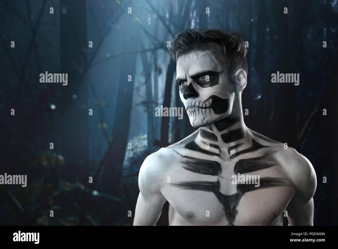 halloween scary skeleton man portrait in studio at dark forest stock