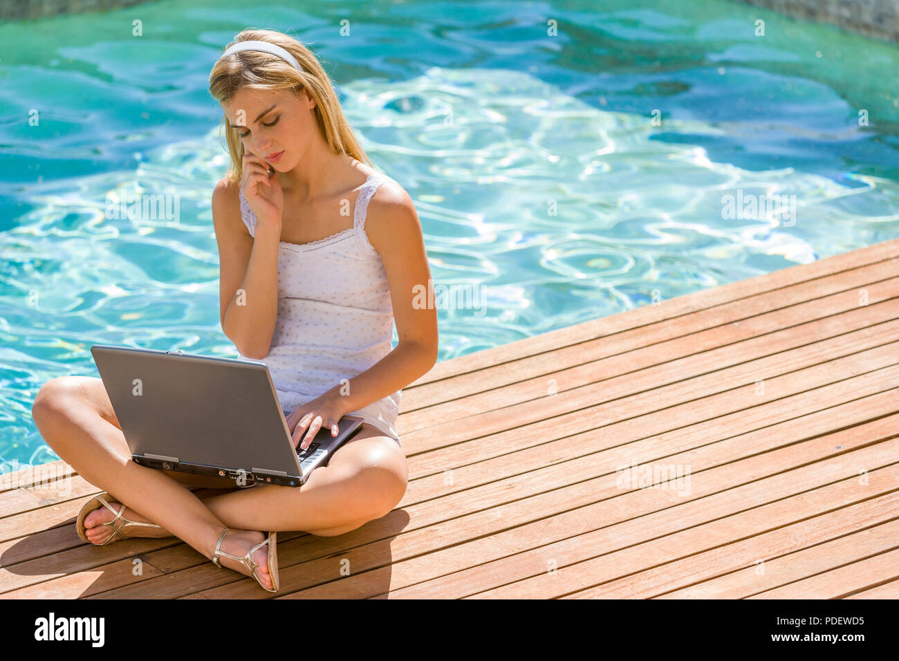 Young woman with laptop sitting by the pool Stock Photo