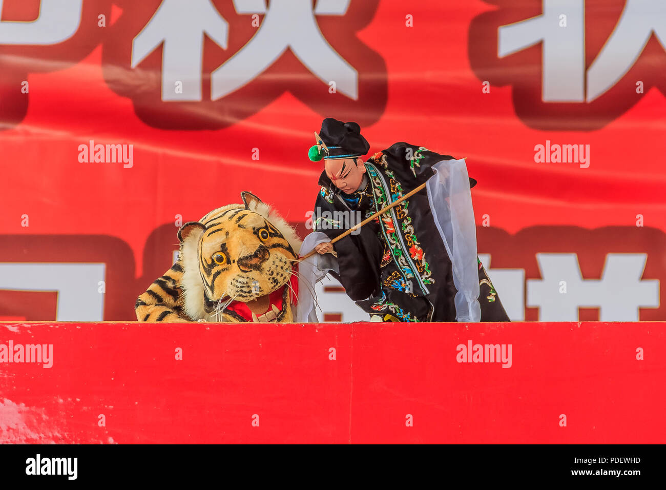 Xiamen, China - September 14, 2013: Chinese puppeteer performing a hand puppet show about Wu Song killing the man-eating tiger based on an ancient Chi - Stock Image
