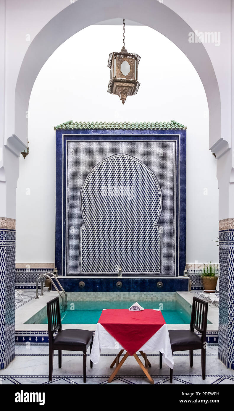 Fes, Morocco - May 11, 2013: Moroccan riad inner courtyard decorated with ornate mosaic and Moorish archway set up with table and chairs with a pool i Stock Photo