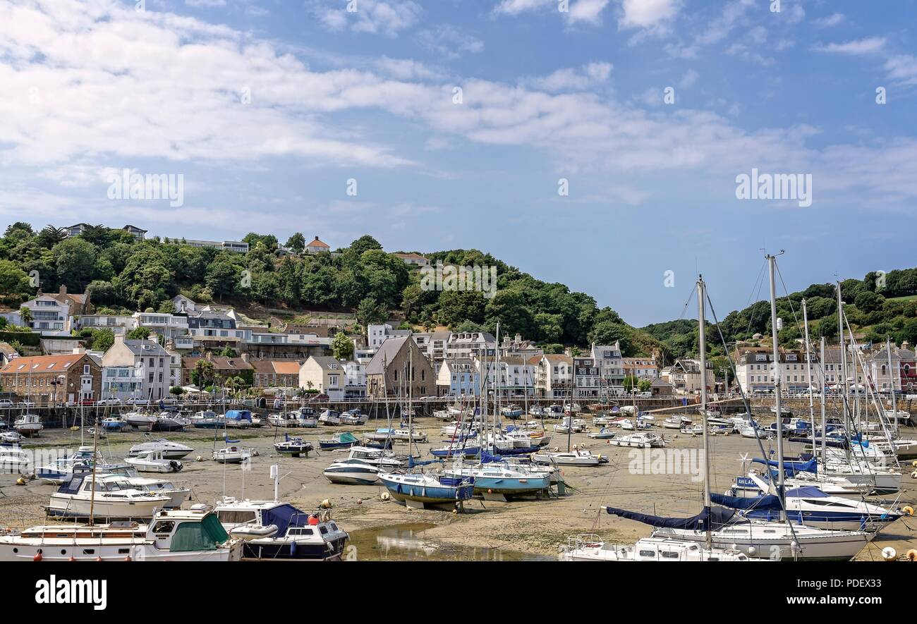 The harbour at St Aubin in Jersey.  The marina of small craft are aground at low tide and buildings surround the harbour. Stock Photo