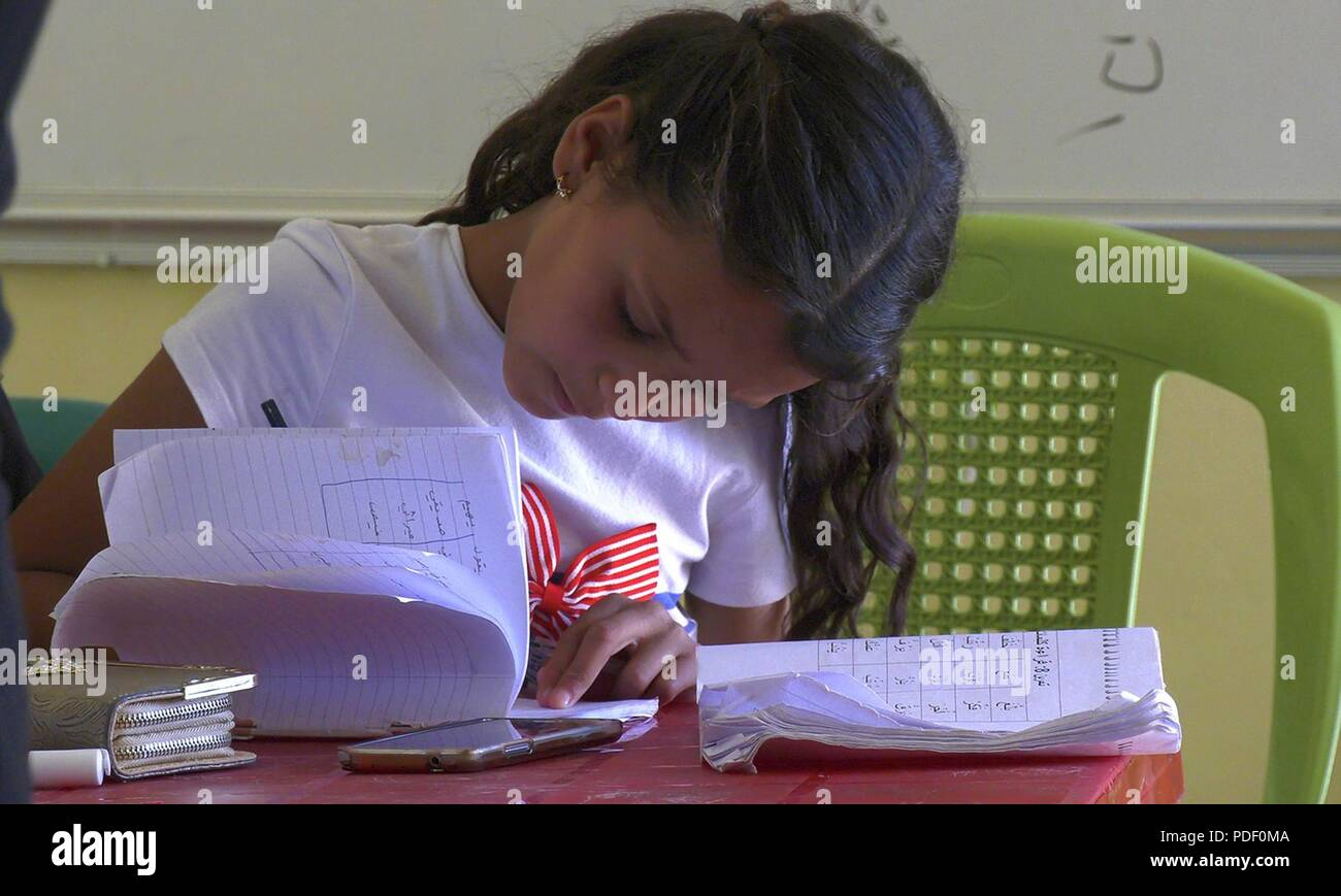 A young student practices writing Arabic during a remedial literacy class offered at Wifaq, a children's school in Ain Issa, Syria, May 16, 2018. Prior to the defeat of ISIS, schools in the area were largely evacuated and shut down for nearly five years. Wifaq opened with the support of the U.S. State Department last year and now offers education for remedial literacy and psychosocial support programs. Wifaq's overall reach continues to expand into the thousands with their psychosocial support mobile units that travel to various locations, including Internally Displaced Persons-camps. The scho - Stock Image