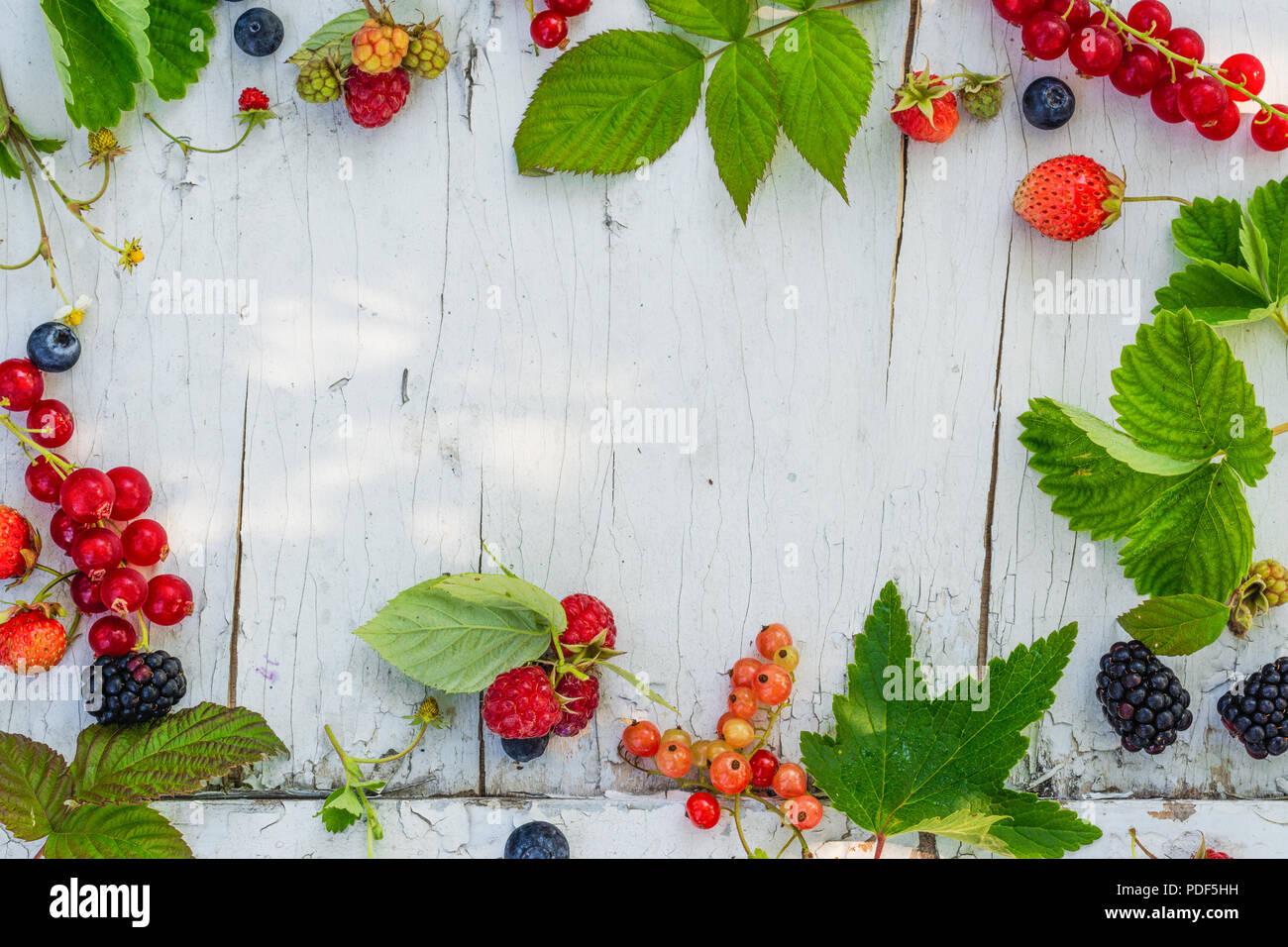 Assortment of summer garden berries on vintage background - Stock Image