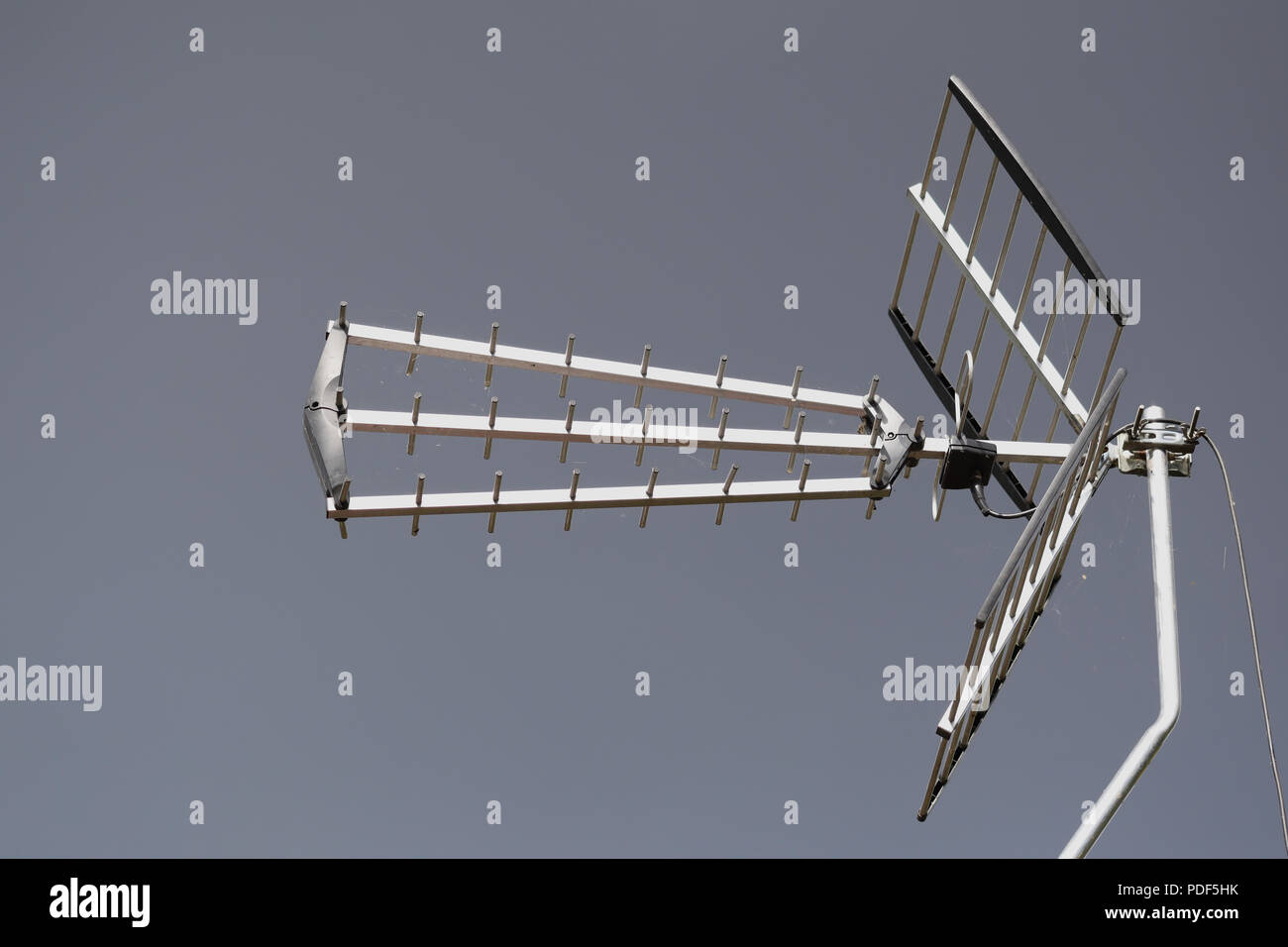 Television aerial against a clear sky background - Stock Image