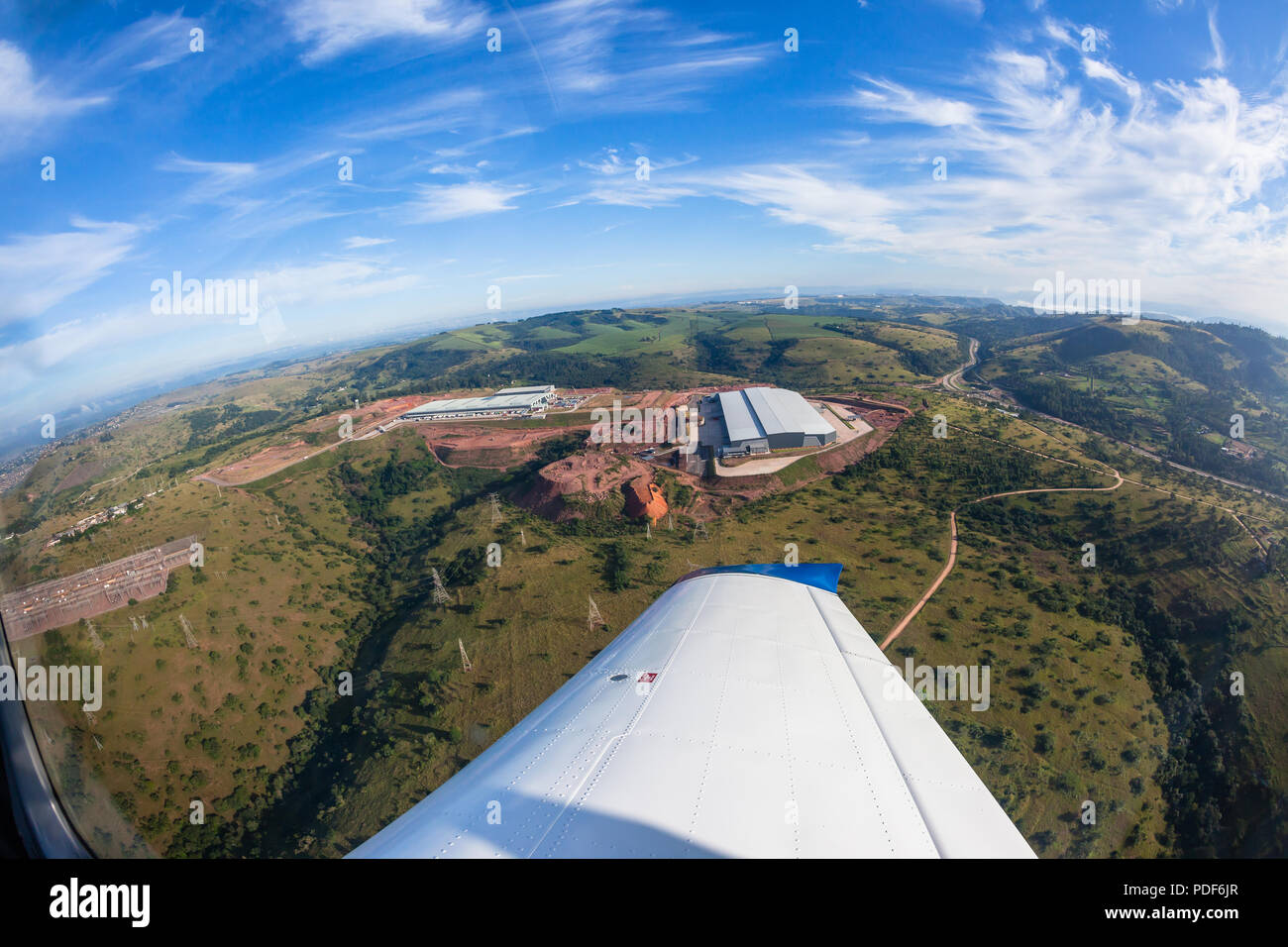 Flying birdseye photo of new built factory warehouses in countryside nearby road highway - Stock Image