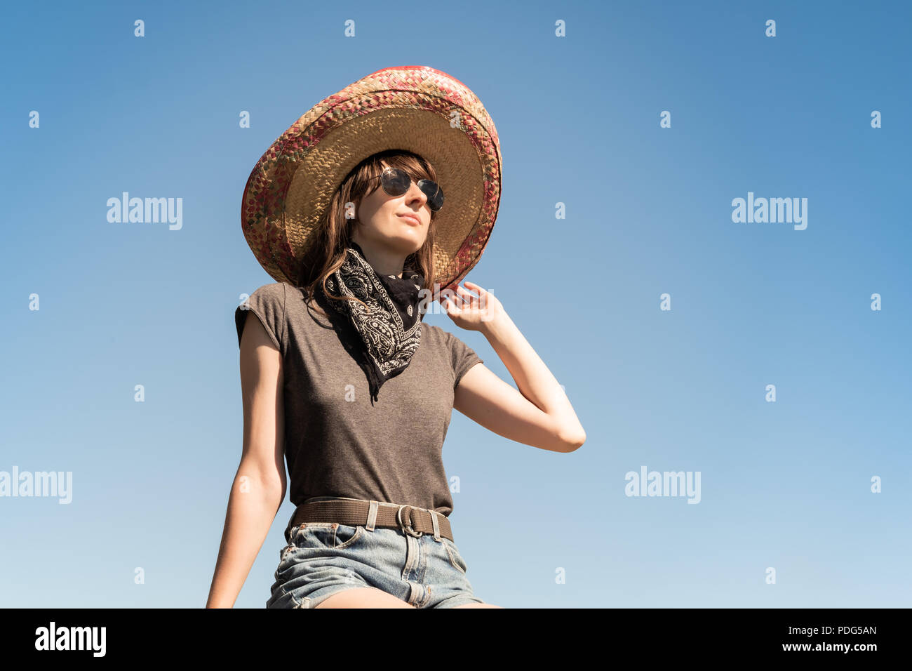 Young beautiful girl in sombrero and bandana dressed up as bandit of gangster. Female person in traditional mexican hat posing as mexico festive symbo - Stock Image
