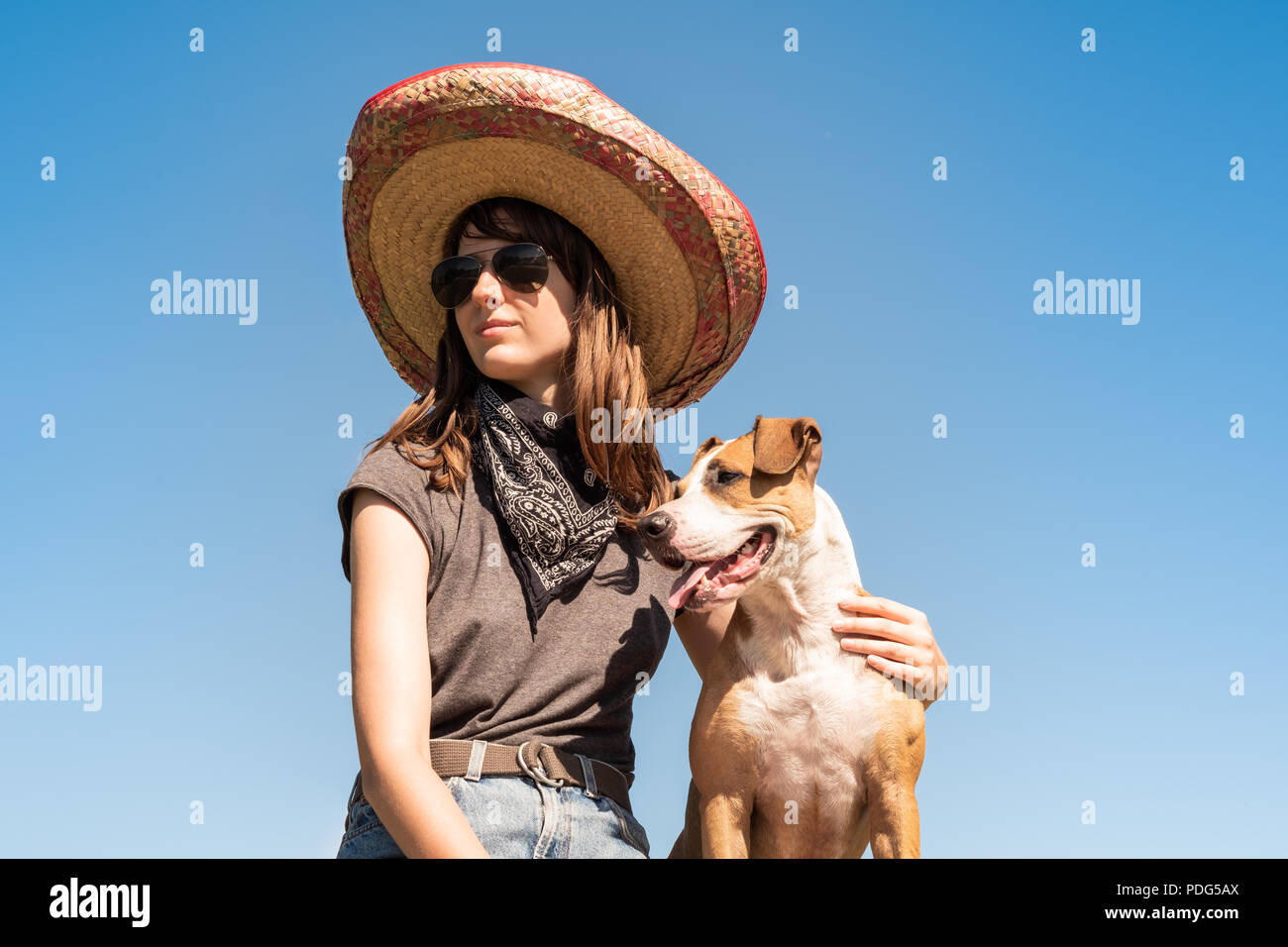 Beautiful girl in mexican hat dressed up as bandit of gangster with dog in cool sunglasses. Female person in sombrero hat and bandana posing with pupp - Stock Image