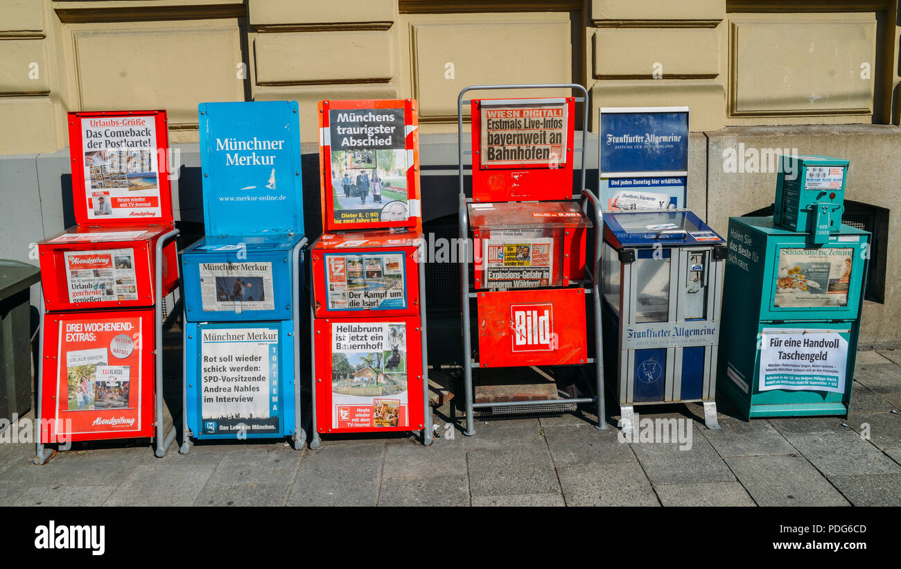 Munich, Germany -July 28, 2018: Detail of some newspaper automatic vending machines in a street of Munich, Germany in a commercial area of the Bavaria - Stock Image