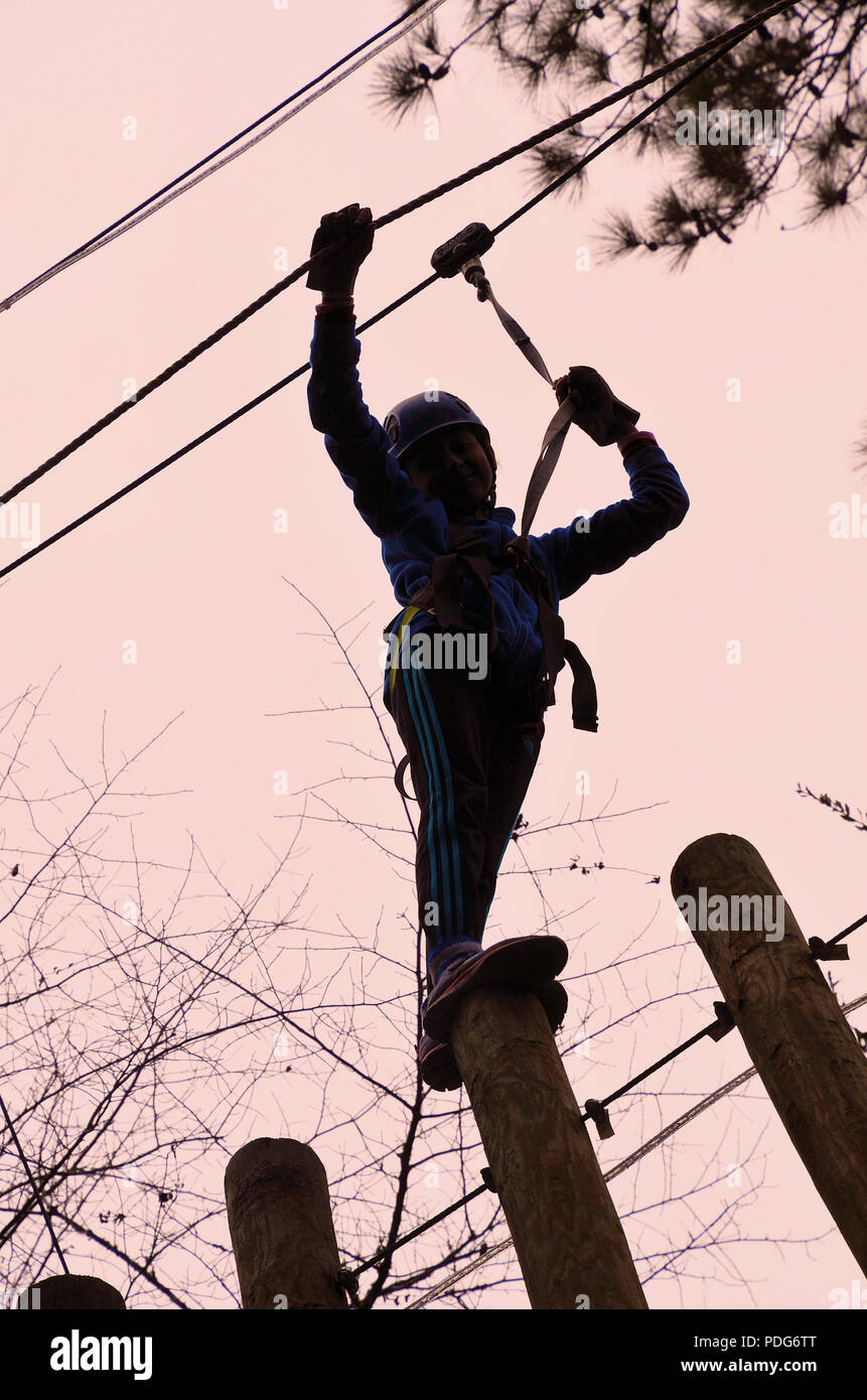 Teenager seen from the ground on the Aerial Adventure Zip Line Park at Hilton Head Island, South Carolina, United States. - Stock Image