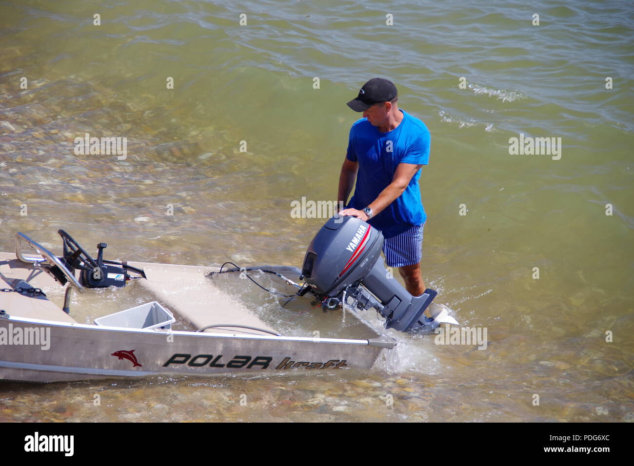 Man with a Partially Flooded Beached Aluminium Boat. Sidmouth beach. East Devon, UK. August, 2018. - Stock Image