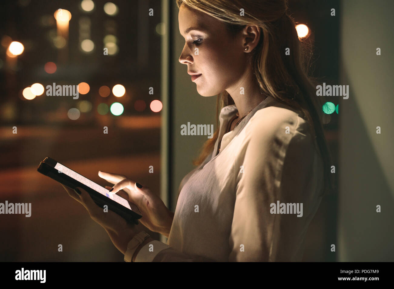 Close up of young businesswoman working on digital tablet in office. Beautiful female working late night in office. - Stock Image