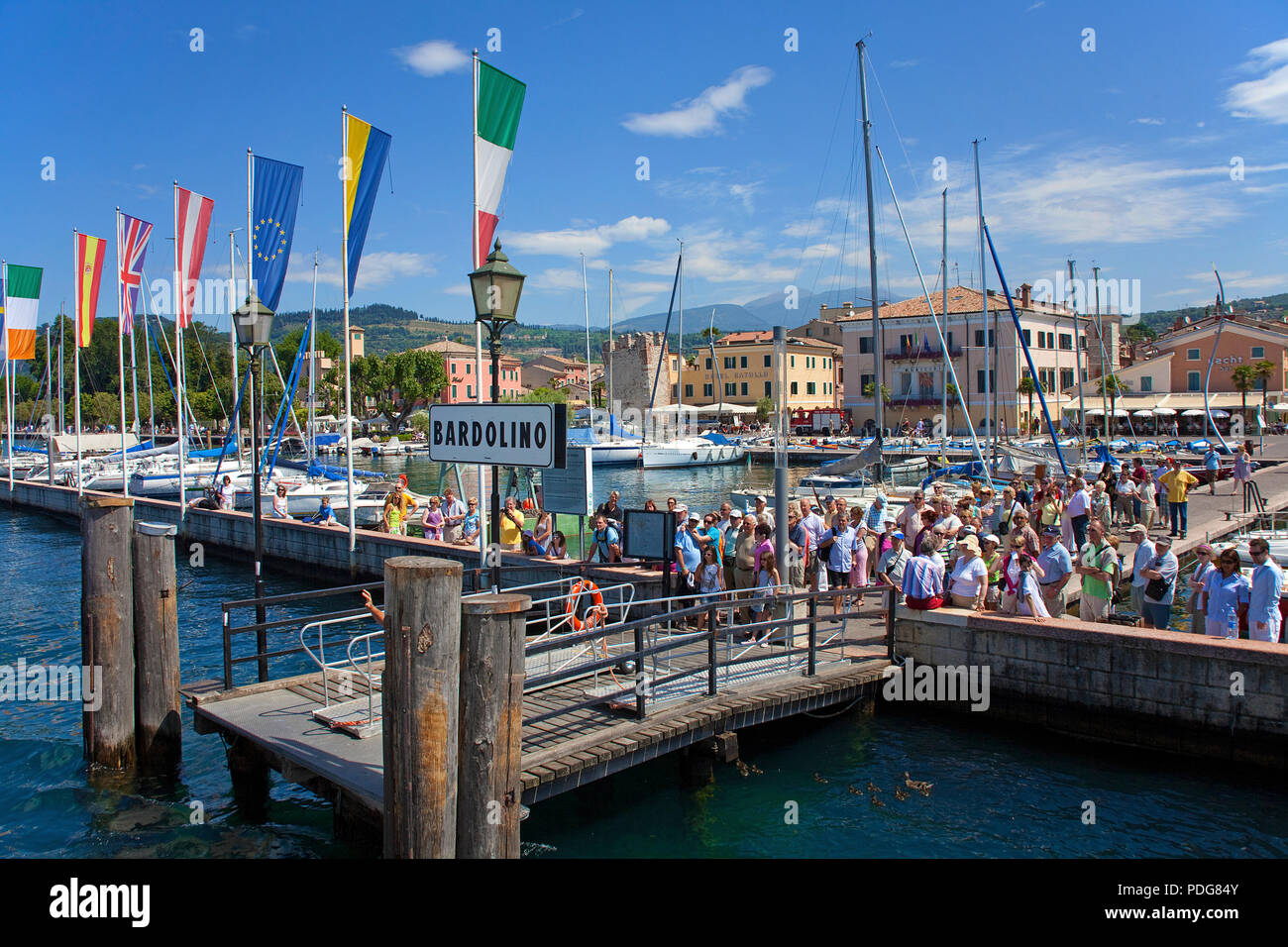 Tourists waiting for excursion boat at the pier of Bardolino, province Verona, Lake Garda, Lombardy, Italy - Stock Image