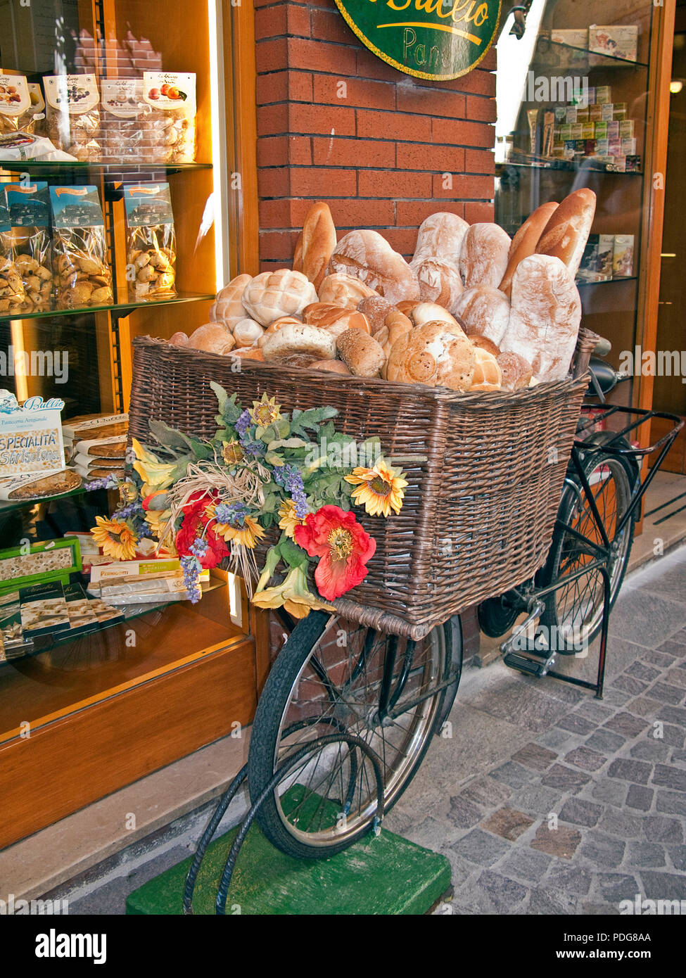 Bicycle with a basket full with bread, decoration in front of a bakery shop, alley at old town of Garda, province Verona, Lake Garda, Lombardy, Italy Stock Photo
