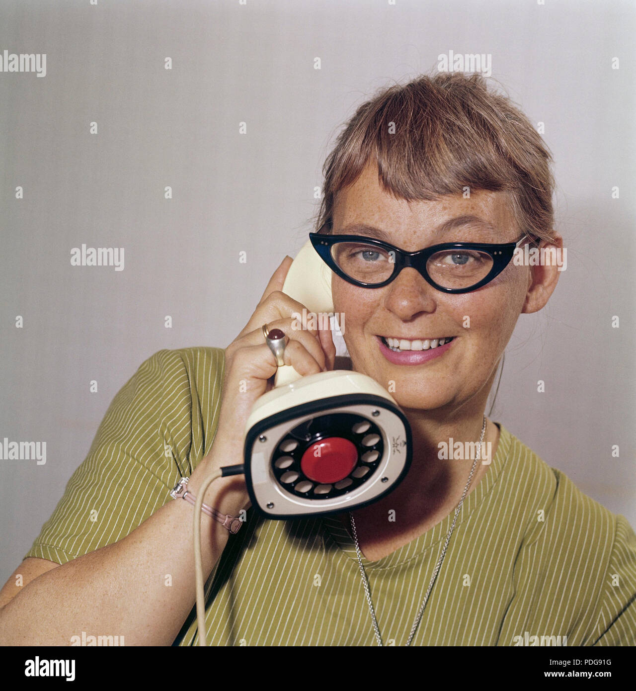 1950s glasses and telephone. A young woman in typical fifties glasses and bows is talking on the telephone.  Swedish on-piece plastic telephone created by Ericsson Company of Sweden. Because of its styling and its influence on future telephone design, the Ericofon is considered one of the most significant industrial designs of the 20th century. The idea was to incorporate the dial and handset into one single unit. The model is also known as the Cobra telephone for its resemblance to a coiled snake, and is now a sought after antique. Stock Photo